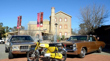 Image: cars and motorbikes in front of old stone building