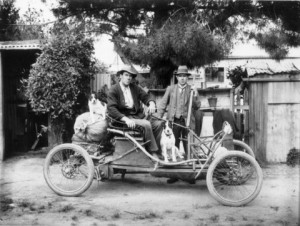 Image: two young men with a dog and hunting equipment in open top old car