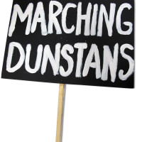 Image: black sign with white text reading 'Marching Dunstans'