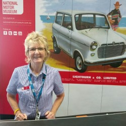 Image: woman standing at desk with motor museum sign behind her